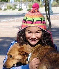 A young ASCMV volunteer holds a dog. She frequently walks dogs for the organization.