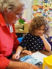 Foster Grandparent volunteer reading with student