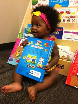 An adorable little girl reading one of our books!